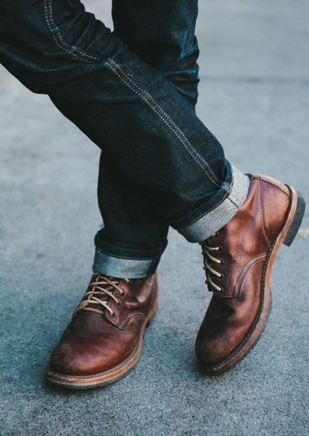 folded jeans and brown boots